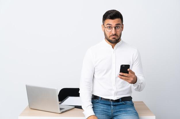 Młody biznesmen trzyma telefon komórkowego smutny