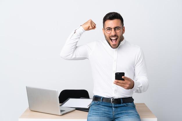 Młody biznesmen trzyma telefon komórkowego świętuje zwycięstwo