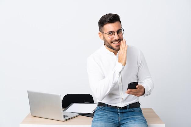Młody biznesmen trzyma telefon komórkowego szepcze coś