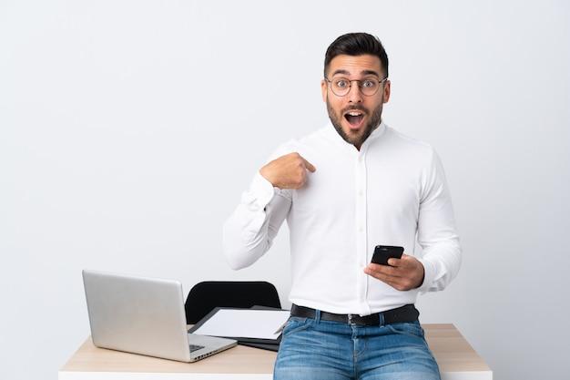 Młody biznesmen trzyma telefon komórkowego z niespodzianka wyrazem twarzy