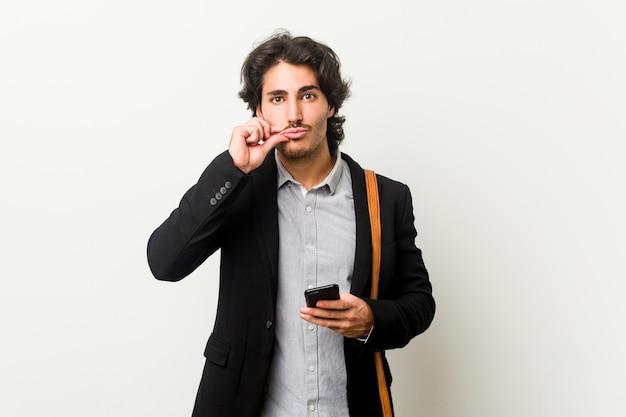 Młody biznesmen trzyma telefon z palcami na ustach, zachowując tajemnicę.