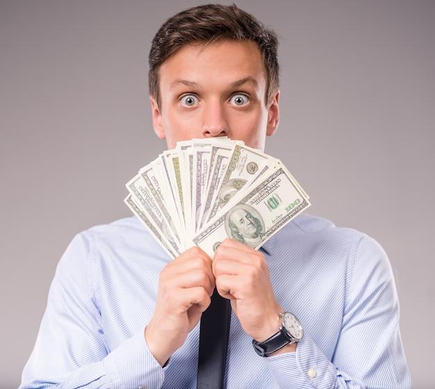 Młody biznesmen trzyma więcej pieniądze.