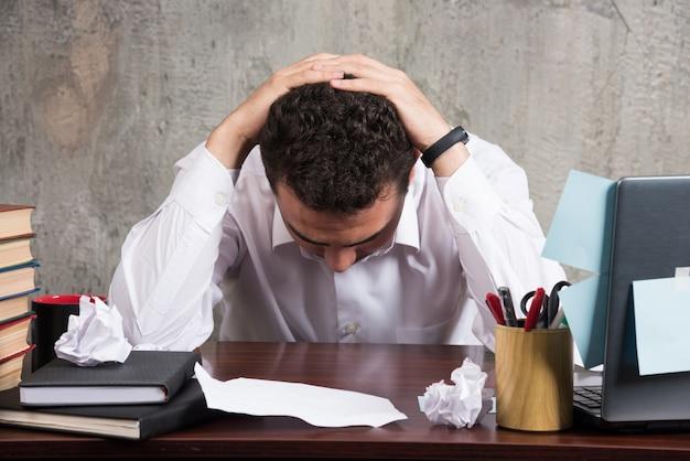 Młody biznesmen trzymając głowę na biurku.