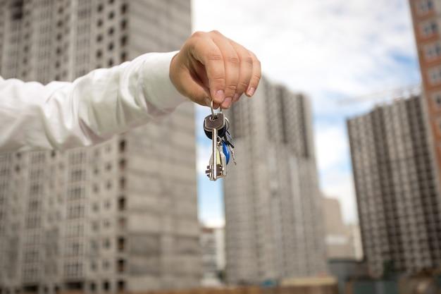 Młody biznesmen trzymający klucze z nowej nieruchomości na placu budowy