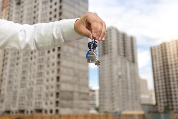 Młody biznesmen trzymający klucze z nowej nieruchomości