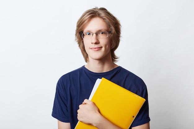 Młody biznesmen ubrany od niechcenia, noszący okulary, mający stylową fryzurę, trzymający w rękach żółtą teczkę z dokumentami lub dokumentami, idący do biura do pracy i przygotowujący raport biznesowy. biznes
