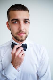 Młody biznesmen ubrany w białą koszulę z krótką brodą nosi czarną muszkę