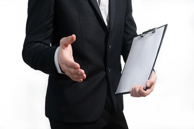 Młody biznesmen ubrany w garnitur, trzymając tablicę znak i dając uścisk dłoni.