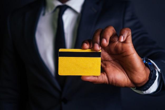 Młody biznesmen udany mężczyzna w stylowym czarnym garniturze klasycznym i fajnych okularach, trzymając żółtą plastikową kartę kredytową w studio na ciemnym tle. koncepcja zakupów