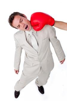 Młody biznesmen uderza z bokserską rękawiczką