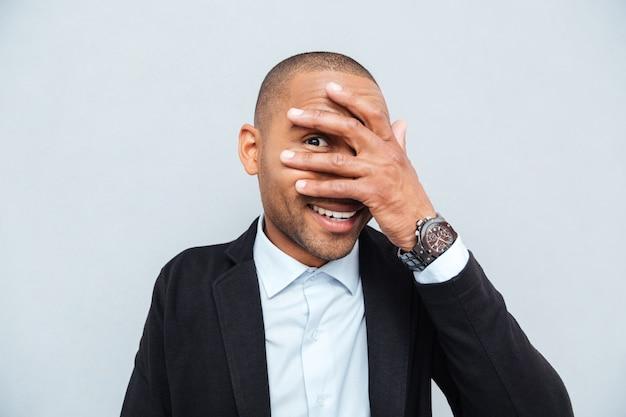 Młody biznesmen ukrywa oczy za jego ręką na białym tle