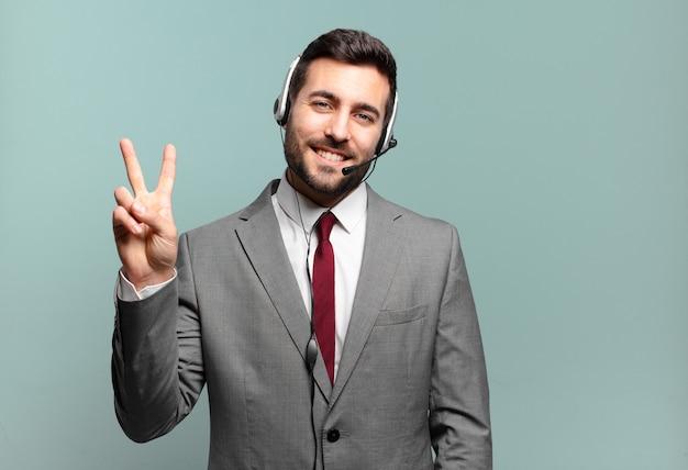 Młody biznesmen uśmiecha się i wygląda przyjaźnie, pokazując numer dwa lub sekundę ręką do przodu, odliczając pojęcie telemarketingu