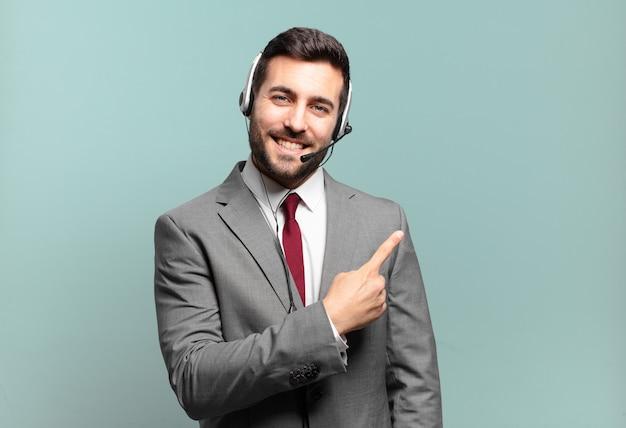 Młody biznesmen uśmiecha się radośnie, czuje się szczęśliwy i wskazuje na bok i do góry, pokazując obiekt w koncepcji telemarketingowej przestrzeni kopii