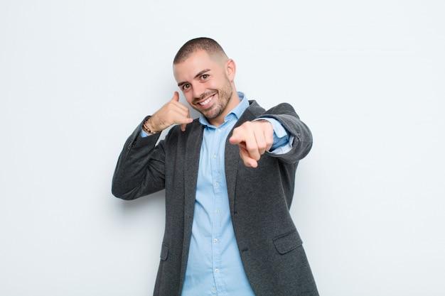 Młody biznesmen uśmiecha się radośnie i wskazuje podczas gdy dzwoniący ty później gestykulujesz