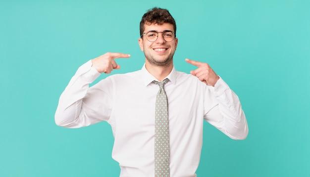 Młody biznesmen uśmiechający się pewnie, wskazując na swój szeroki uśmiech, pozytywną, zrelaksowaną, zadowoloną postawę