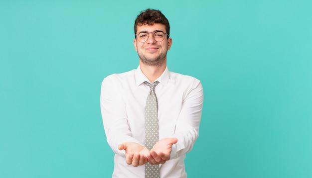 Młody biznesmen uśmiechający się radośnie z przyjaznym, pewnym siebie, pozytywnym spojrzeniem, oferujący i pokazujący przedmiot lub koncepcję