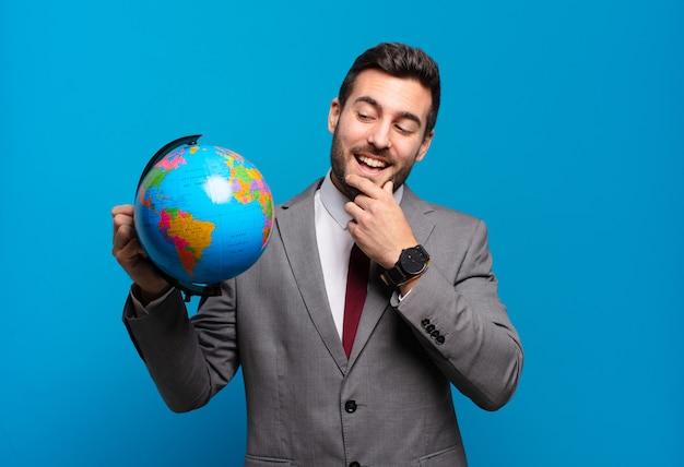 Młody biznesmen uśmiechający się ze szczęśliwym, pewnym siebie wyrazem twarzy z ręką na brodzie, zastanawiający się i patrzący w bok, trzymający mapę świata
