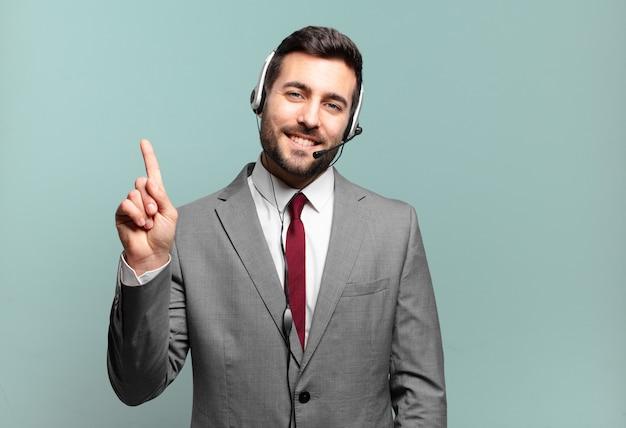 Młody biznesmen uśmiechnięty i wyglądający przyjaźnie, pokazując numer jeden lub pierwszy z ręką do przodu, odliczając koncepcję telemarketingu