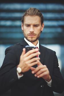Młody biznesmen używa jego telefon