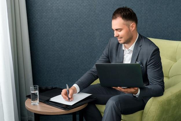 Młody biznesmen używa laptopa i pracuje z dokumentami, siedząc w pokoju hotelowym z walizką.