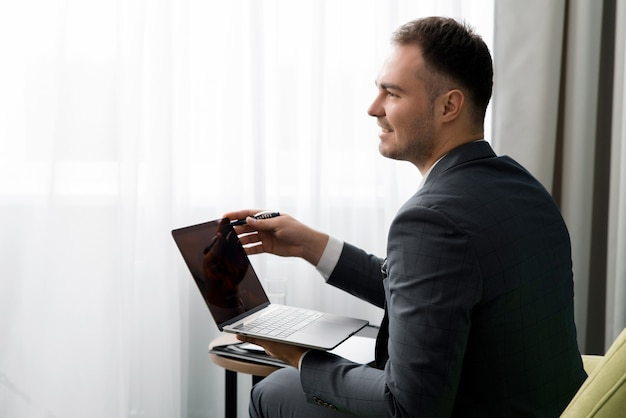 Młody biznesmen używa laptopa siedząc w pokoju hotelowym z walizką.