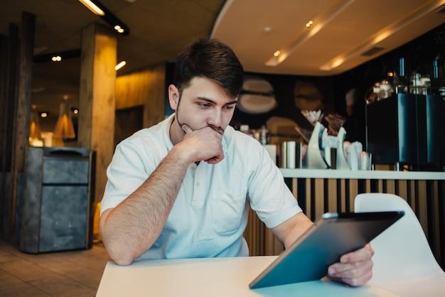 Młody biznesmen używa pastylkę w kawiarni
