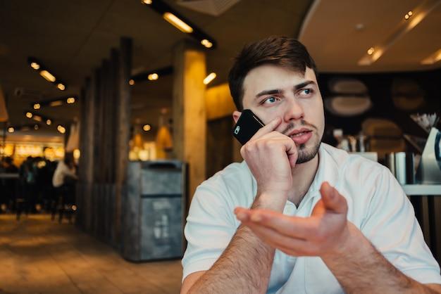 Młody biznesmen używa telefon komórkowego w kawiarni