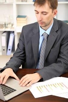 Młody biznesmen w biurze w swoim miejscu pracy