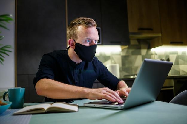 Młody biznesmen w czarnej masce antywirusowej, pracujący w domu, siedzący przy kuchennym stole z laptopem. praca w domu w kwarantannie