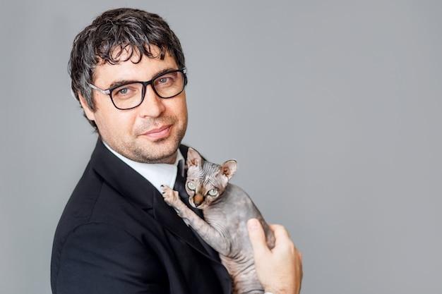 Młody biznesmen w czarnym garniturze i okularach trzyma w rękach kota rodowodowego sfinksa.