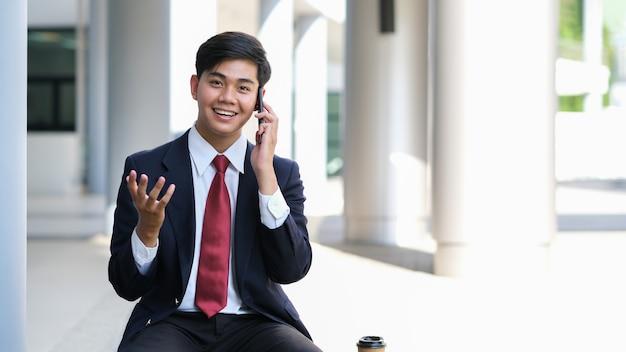 Młody biznesmen w czarnym garniturze rozmawia przez telefon z partnerami.