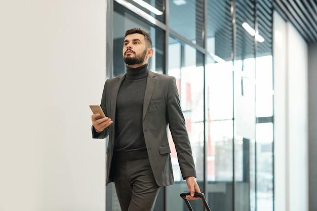 Młody biznesmen w formalnej odzieży, ciągnąc walizkę w kierunku wyjścia przez lotnisko podczas podróży