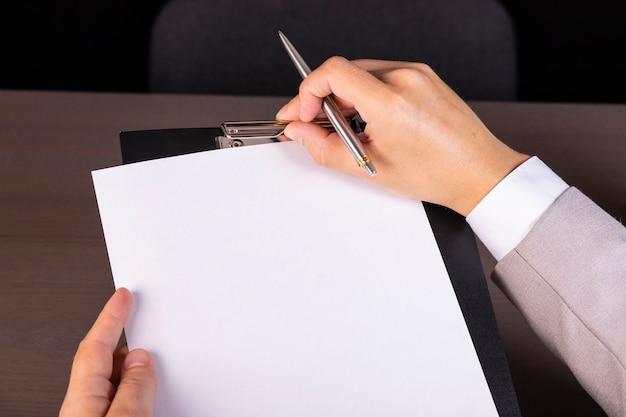 Młody biznesmen w formalnym garniturze robienia notatek