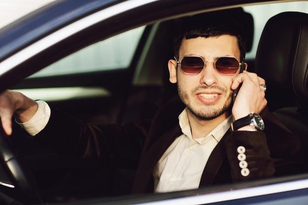 Młody biznesmen w garniturze i czarnych okularach rozmawia przez telefon w samochodzie. wygląd biznesowy. jazda próbna nowego samochodu