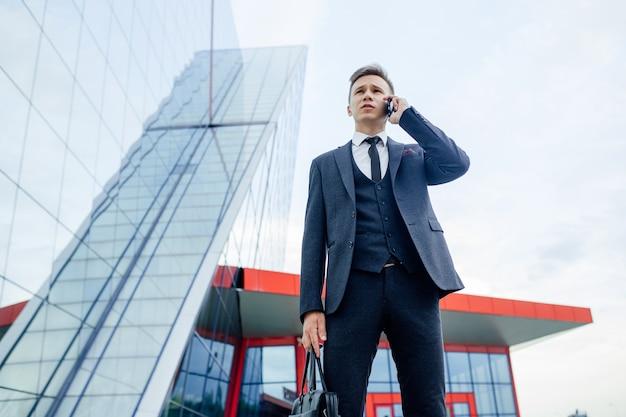 Młody biznesmen w garniturze i pod krawatem stoi na zewnątrz, rozmawiając przez telefon.