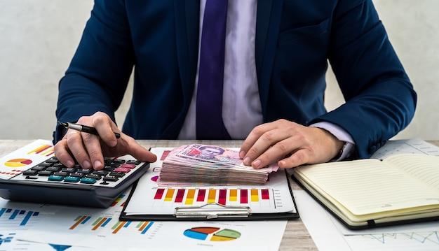Młody biznesmen w garniturze liczy hrywny i pracuje z wykresami i dokumentami jako miesięczny dochód netto