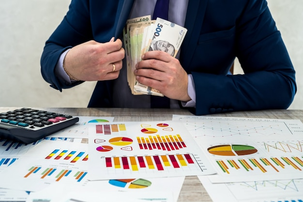 Młody biznesmen w garniturze liczy pieniądze w hrywnach i pracuje z wykresami i dokumentami jako miesięczny dochód netto. pojęciem pieniądza jest pensja lub korupcja. praca w biurze.