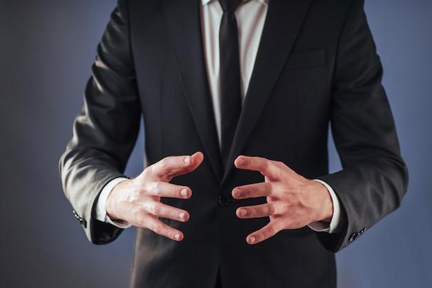 Młody biznesmen w garniturze pokazuje rękę na ciemnym tle na białym tle