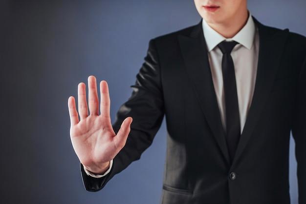 Młody biznesmen w garniturze pokazuje rękę