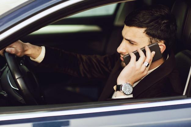 Młody biznesmen w garniturze rozmawia przez telefon w samochodzie. wygląd biznesowy. jazda próbna nowego samochodu