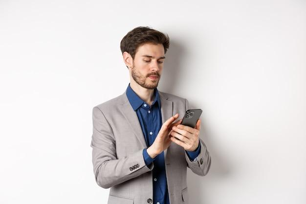 Młody biznesmen w garniturze wiadomości tekstowych na telefon komórkowy, patrząc na smartfonie, stojąc na białym tle.