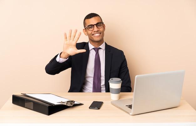 Młody biznesmen w jego biurze z laptopem i innymi dokumentami liczy pięć z palcami