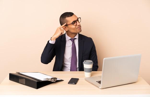 Młody biznesmen w jego biurze z laptopem i innymi dokumentami robi gestowi szaleństwa kładzenie palca na głowie