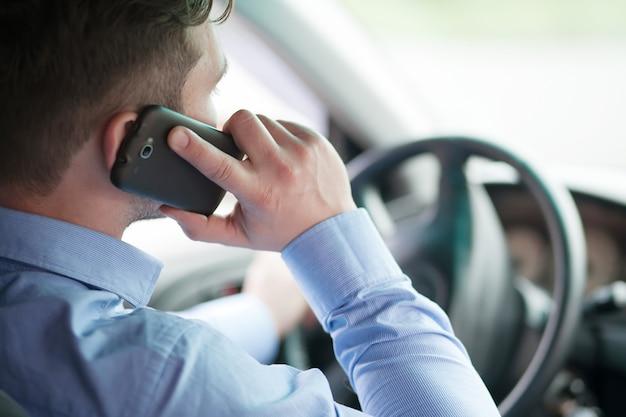 Młody biznesmen w jego samochodzie za kierownicą rozmawia przez telefon komórkowy
