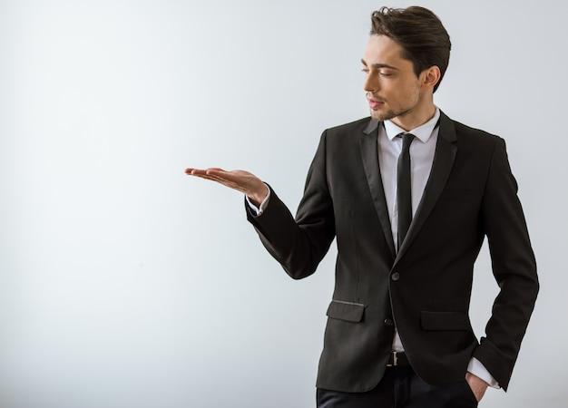 Młody biznesmen w klasycznym kostiumu utrzymuje palmę up.