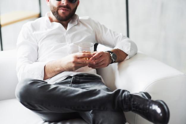 Młody biznesmen w klasycznym stroju siedzi na kanapie ze szklanką whisky w dłoni
