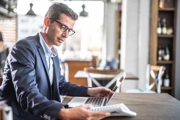 Młody biznesmen w marynarce i okularach czyta w stołówce z komputerem na stole przed nim.