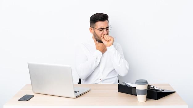 Młody biznesmen w miejscu pracy cierpi na kaszel i źle się czuje