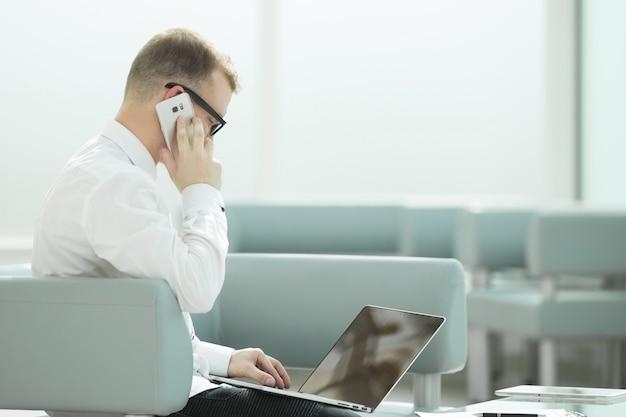 Młody biznesmen w miejscu pracy w jego biurze. ludzie i technologia