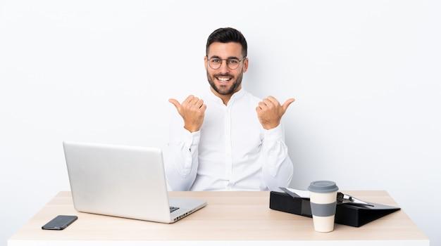 Młody biznesmen w miejscu pracy z aprobatami gestykuluje i ono uśmiecha się